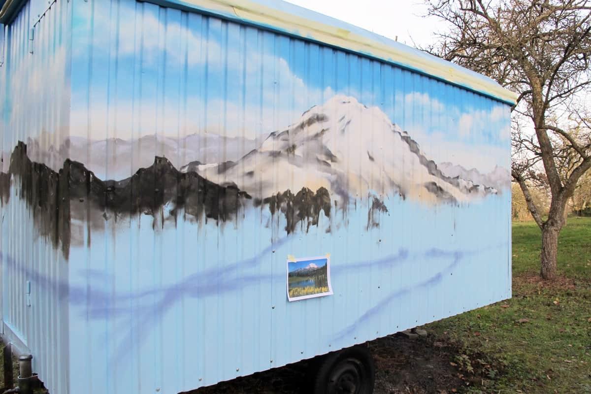 """Wir von GRAFFITI STUTTGART wurden von einer Kundin damit beauftragt die Aussenwände ihres frisch renovierten Bauwagens mit dem Thema """"Alpenpanorama"""" zu gestalten."""