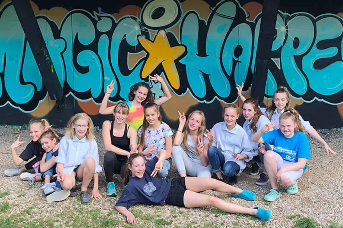 Um den Graffiti Kindergeburtstag von Salome gebührend zu feiern, haben wir von Graffiti Stuttgart mit ihren Gästen ein cooles Graffiti an der Außenwand vom Camp Feuerbach gemalt. Am Tag der Malaktion grundierte Micha die zu besprühende Fläche mit Wandfarbe, um dann die zuvor verabredeten Motive auf der Betonmauer vor zu skizzieren. Anschließend malte Salome mit ihren Freunden den Graffiti Style mit allen Buchstaben und Elementen farbig aus. Danach sprühte Micha noch die Konturen Outlines und die Lichteffekte.