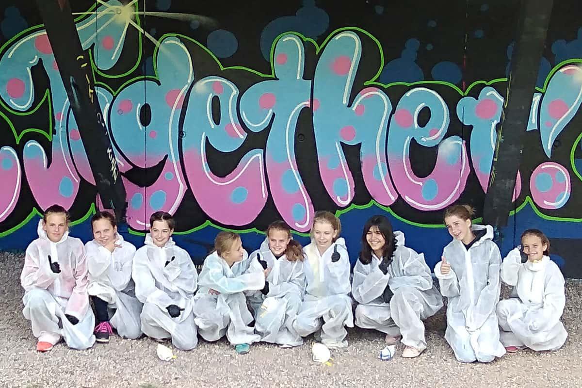 Um den Kindergeburtstag von Frederike gebührend zu feiern, haben wir von Graffiti Stuttgart mit ihren Gästen ein cooles Graffiti an der Außenwand vom Camp Feuerbach gemalt. Am Tag der Malaktion grundierte Dominik die zu besprühende Fläche mit Wandfarbe, um dann die zuvor verabredeten Motive auf der Betonmauer vor zu skizzieren. Anschließend malte Frederike mit ihren Freunden den Graffiti Style mit allen Buchstaben und Elementen farbig aus. Danach sprühte Dominik noch die Konturen und die Lichteffekte.