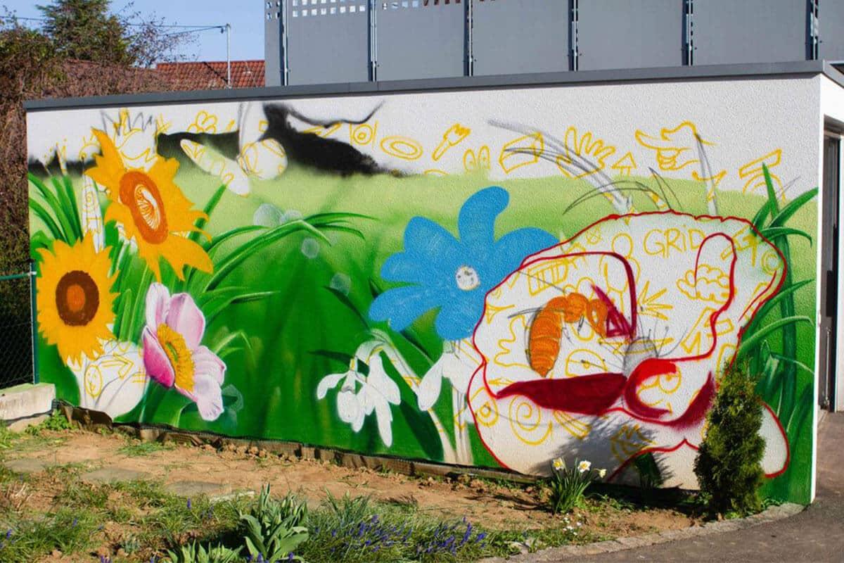 Graffiti Stuttgart wurde für die Gestaltung einer Garagenmauer beauftragt. Passend zum Blumengarten mit dazugehörigem Bienenhotel besprühte Chris die weiße Garagenwand mit einer farbenfrohen Blumenwiese inklusive Biene und Schmetterling.