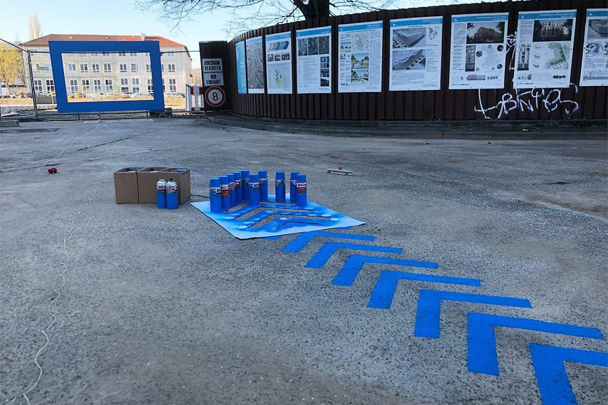 """In Form von Pfeilen und Kreis hat Patrick ein Blaues Band für die Wegführung zur Werkschau am Bauzaun des Neubauprojekts """"Quartier am Wiener Platz"""" gesprüht."""