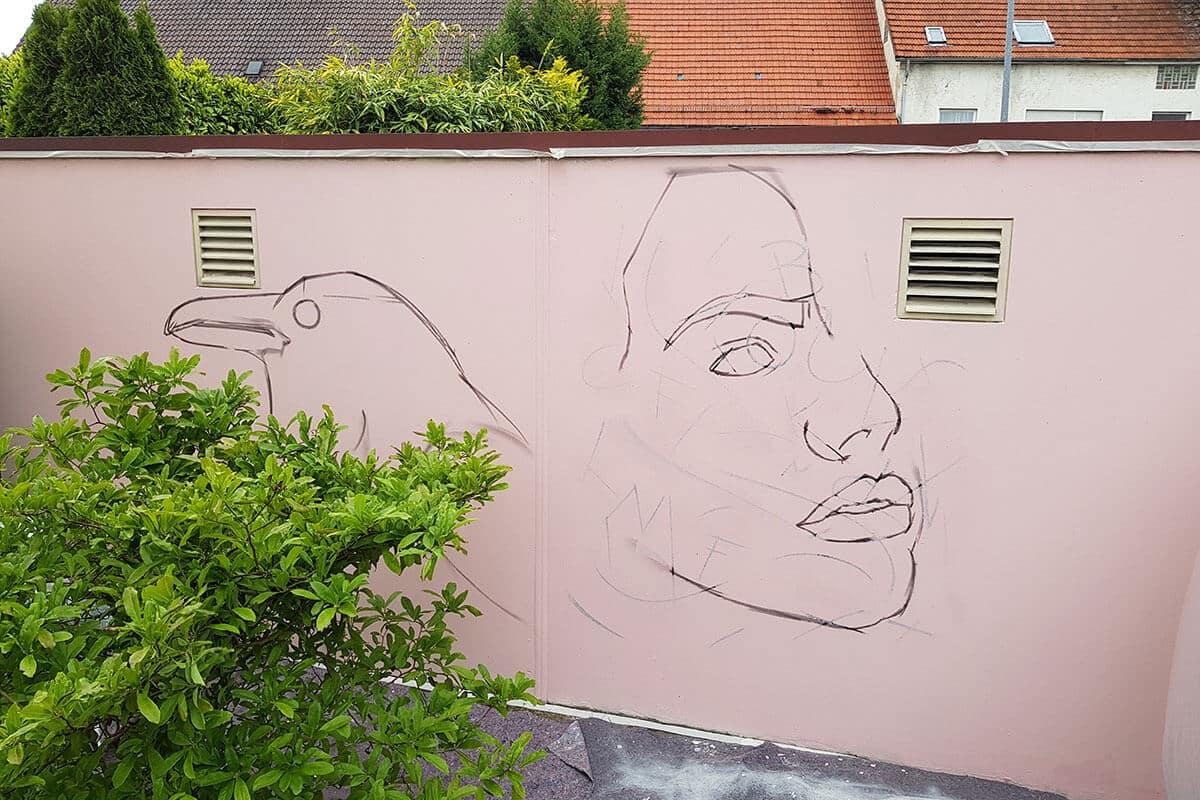 Zunächst grundierte Bernad die Blanko-Wand und skizzierte einen Raben und eine Frau auf die blassrosa Mauer. Anschließend besprühte er in seinem Style die Flächen und Konturen.